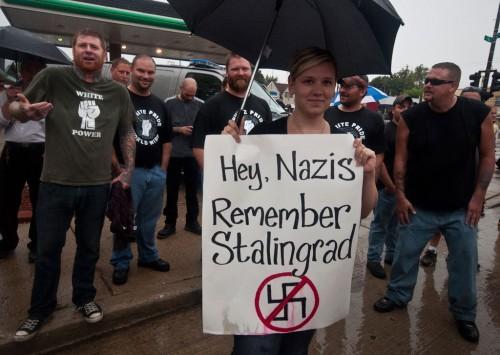 """Les artistes trolls antifascistes Jacob Flom et Missy Gaido mettent en scène cette photographie de cette dernière devant les nazis tenant une pancarte """"Hé nazis, souvenez-vous de Stalingrad""""."""